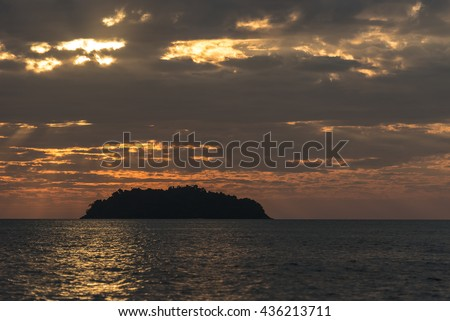 silhouette of the island to the shining sea under dramatic dark clouds that make their way through the rays of sunlight at sunset