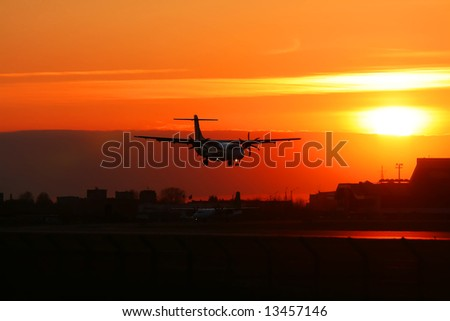 Silhouette of the landing plane at sunset. - stock photo