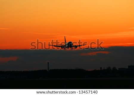 Silhouette of the landing plane on a sunset. - stock photo