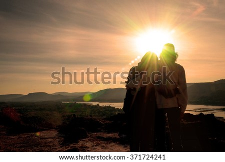 Silhouette of the lover standing on the hilltop during sunrise.