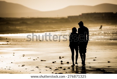 Silhouette of the loving couple, walking on the beach - stock photo