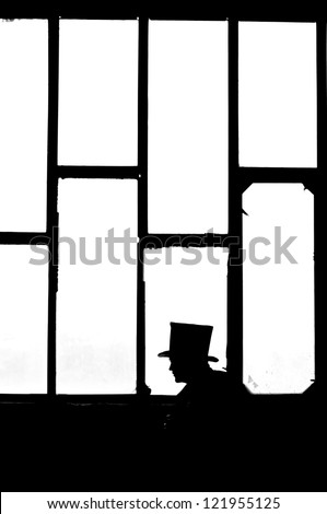 Silhouette of the man in black at the window - stock photo