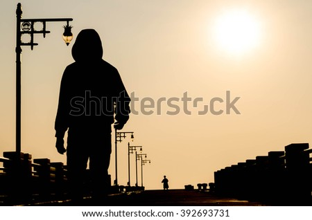 silhouette of the man in sportswear with a hood at sunset