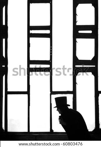 Silhouette of the Man in the black coat and hat in the dark interior near the meshed window. Monochrome photo - stock photo