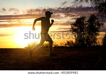 Silhouette of the Man running on the Sunset Background