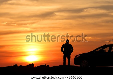 Silhouette of the man standing near to car and looking at a sunset