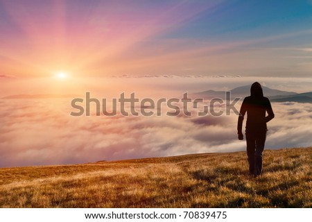 silhouette of the man walking above the clouds on the sunrise - stock photo
