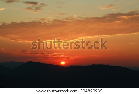 Silhouette of the mountain hills against setting sun and colorful sunset sky - stock photo