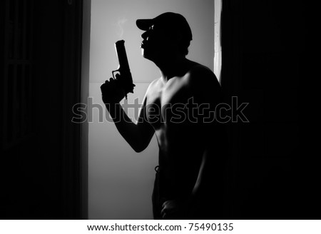 Silhouette of the muscular man with fuming gun in the dark interior. Monochrome photo