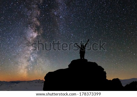Silhouette of the person on the high rock at Milky Way background - stock photo