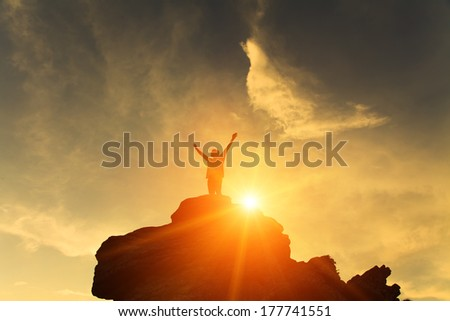 Silhouette of the person on the high rock at sunset - stock photo