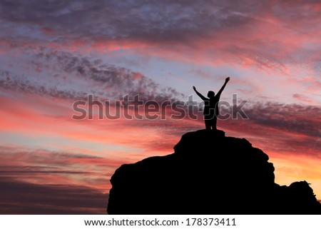Silhouette of the person on the high rock at sunset