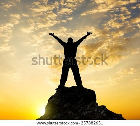 Silhouette of the person standing on a rock in beams of a decline. The concept of success of glory.  - stock photo