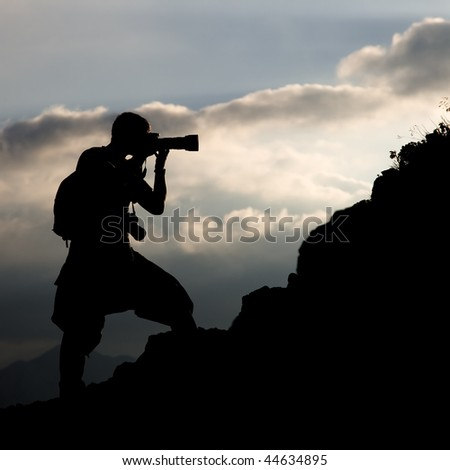 Silhouette of the photographer on a hillside on a background of clouds - stock photo