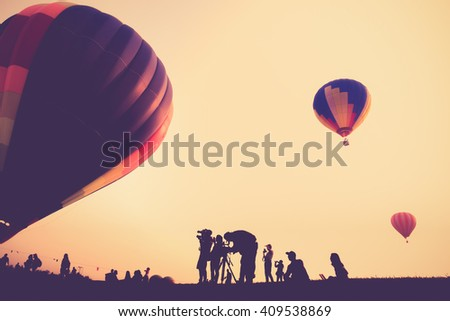 Silhouette of the photographer shoots a photo of hot air balloon vintage color - stock photo