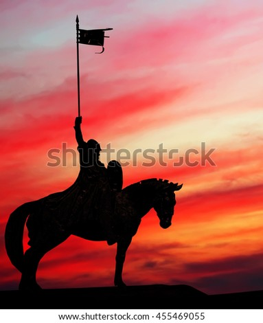 Silhouette of the rider on the horse, holding a pennant (flag) at fiery red sunset sky