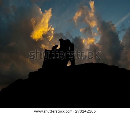 silhouette of the ruins of a medieval castle on a background of storm clouds - stock photo