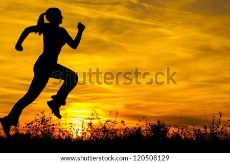 Silhouette of the running girl at sunrise. - stock photo