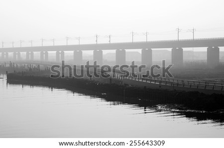 Silhouette of the Shanghai high-speed railtrack across Yangcheng lake, China, processed in monochrome. - stock photo