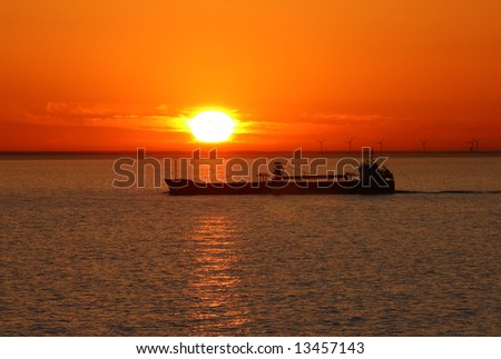 Silhouette of the ship on a sunset. - stock photo