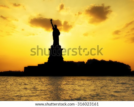 Silhouette of the Statue of Liberty at sunset with reflections on the ocean - stock photo