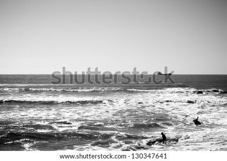 Silhouette of the surfer riding a wave and doing tricks, black and white photo