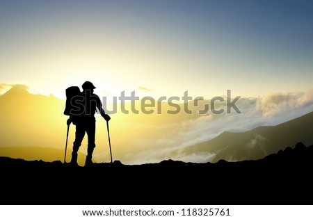 Silhouette of the tourist on background of sunshine. Concept and idea - stock photo