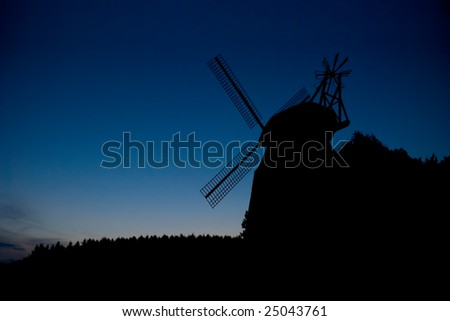 Silhouette of the windmill at dusk - stock photo