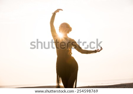 Silhouette of the woman dancing at the beach during beautiful sunrise - stock photo