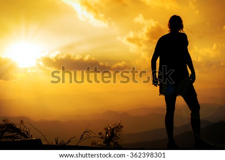 Silhouette of the woman on top of  mountain at sunset