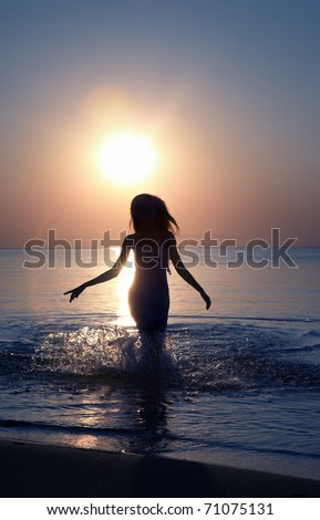 Silhouette of the woman running in the water during sunset. Natural light and colors