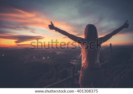Silhouette of the woman spreading arms with her thumbs up, standing high on the viewpoint with breathtaking view over fields in sunset light.Chocolate Hills, Bohol Island, Philippines.