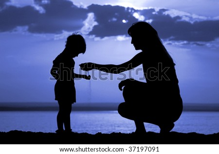 Silhouette of the women to pour sand in hand child on moon night
