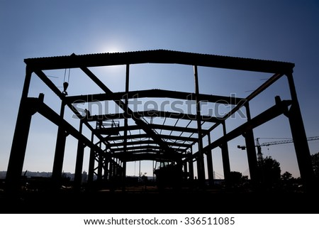 Silhouette of the workers dissembling industrial warehouse. Dissembling industrial constructions. - stock photo