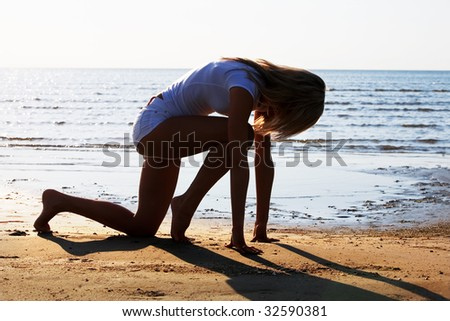 Silhouette of the young girl starting  to run on the seacoast - stock photo