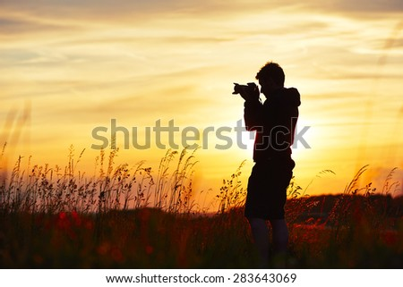 Silhouette of the young photographer at the sunset. - stock photo