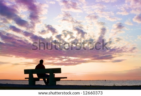 silhouette of thinking man on bench by sunset - stock photo