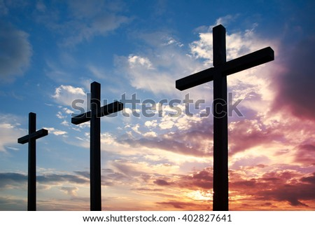 Silhouette of three crosses on a background of the setting sun
