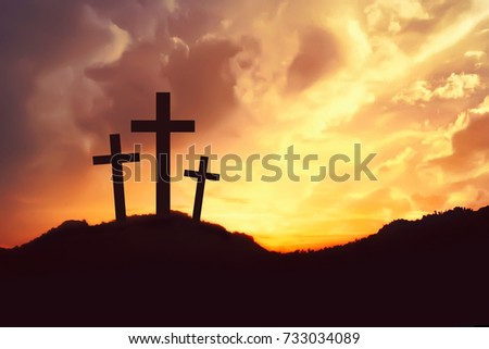 Silhouette of three crosses symbol on the mountain peak with dramatic cloud on the sky at sunrise