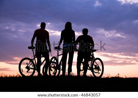 Silhouette of three cyclists on the background of a beautiful sunset - stock photo