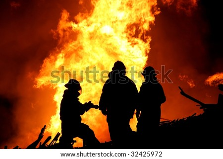 Silhouette of three firemen fighting a huge fire of burning timber - stock photo