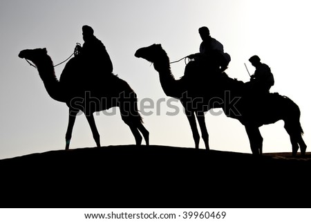 silhouette of three man riding dromedaries in the desert - stock photo
