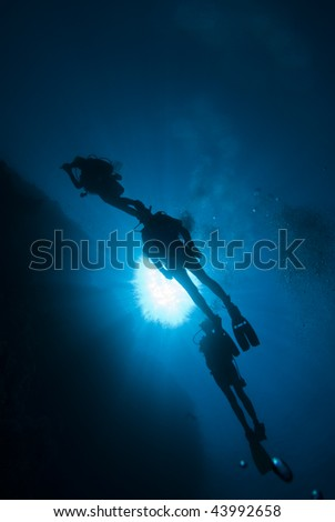 Silhouette of three scuba divers in blue water.