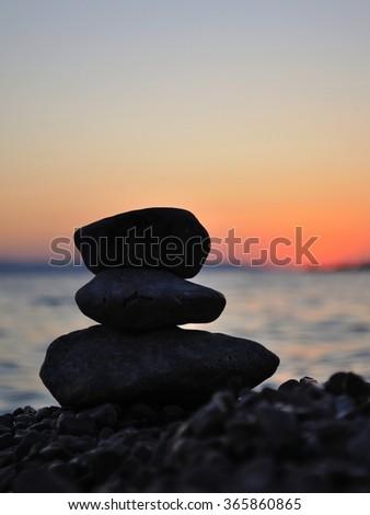 Silhouette of three zen rocks on the beach at sunset. Podgora, Croatia - stock photo