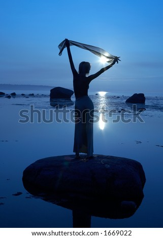 silhouette of topless girl at the seashore - stock photo