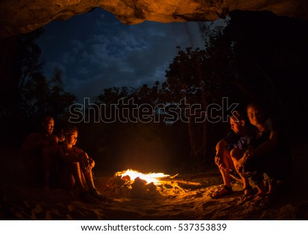 Silhouette of tourist girl around campfire at night on the river shore
