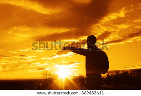 silhouette of tourist in a mountains at the sunset rays. Show finger at far away. nature background
