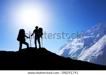 Silhouette of tourist on mountain peak. Sport and active life concept - stock photo
