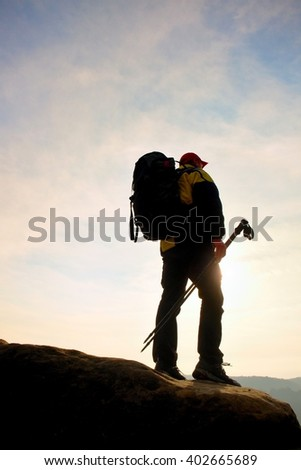 Silhouette of tourist with red cap and  poles in hand. Hiker with big backpack stand on rock. Sunny spring daybreak in rocky mountains. - stock photo