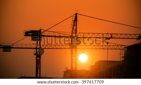 Silhouette of tower crane on a construction site at sunset - stock photo